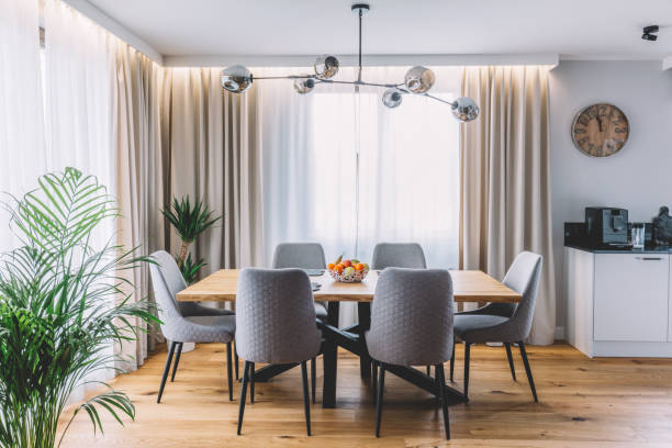 Dining room with wooden table and floor in modern apartment. stock photo