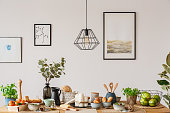 Dining room interior with white wall, art prints and a wooden table with bread and fruit