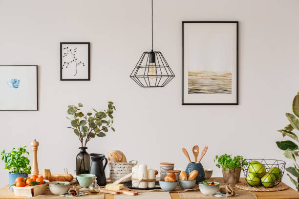 Dining room with wooden table Dining room interior with white wall, art prints and a wooden table with bread and fruit amulet stock pictures, royalty-free photos & images