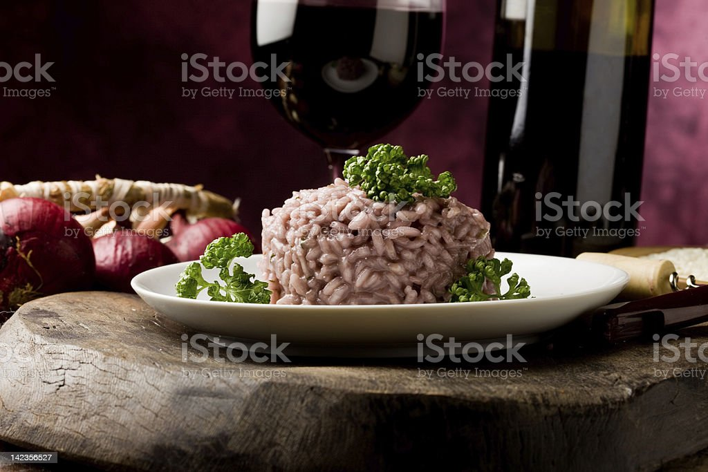 Dining setup of plate of risotto and a glass of red wine stock photo