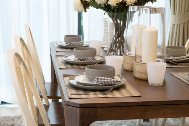 dining table and comfortable chairs in modern home with elegant table setting stock photo