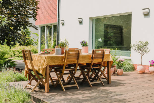 Dining table covered with orange tablecloth standing on wooden terrace in green garden stock photo