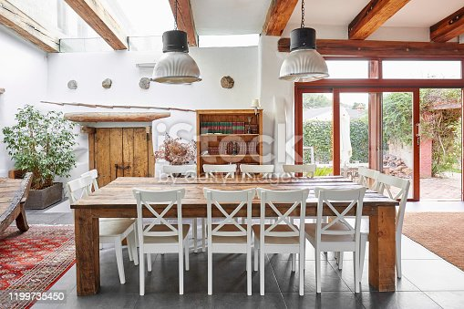 Bright dining area with big dining table and chairs in a Spanish modern farmhouse.