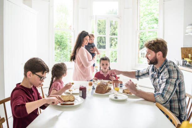 Dining table in modern home with family eating breakfast, mother carrying son stock photo