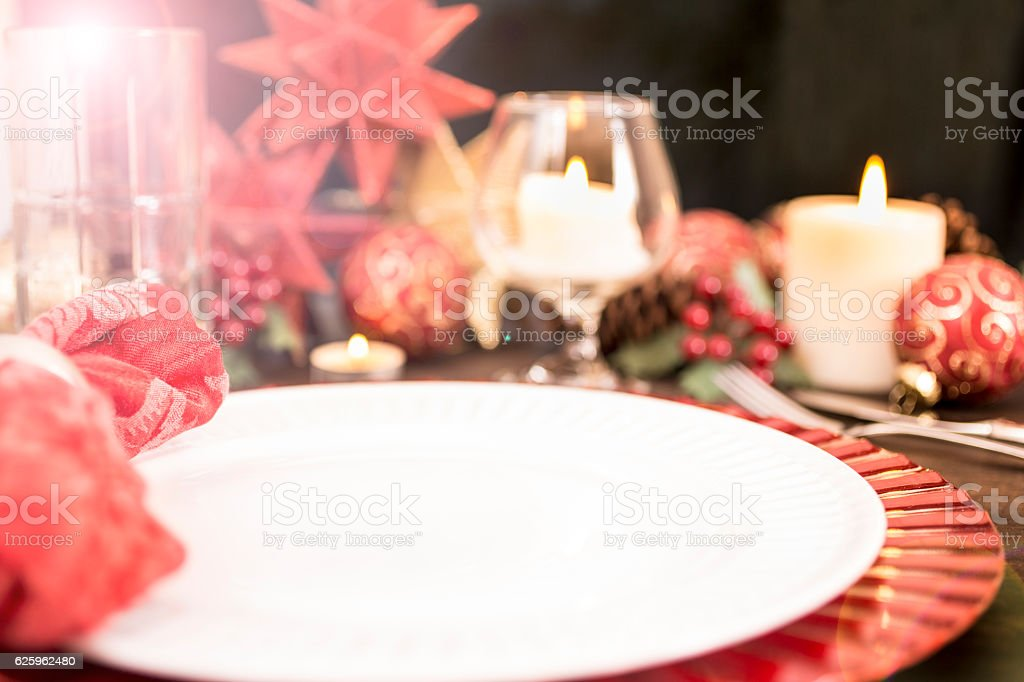 Beautiful Christmas place setting on dining table. Napkin in...