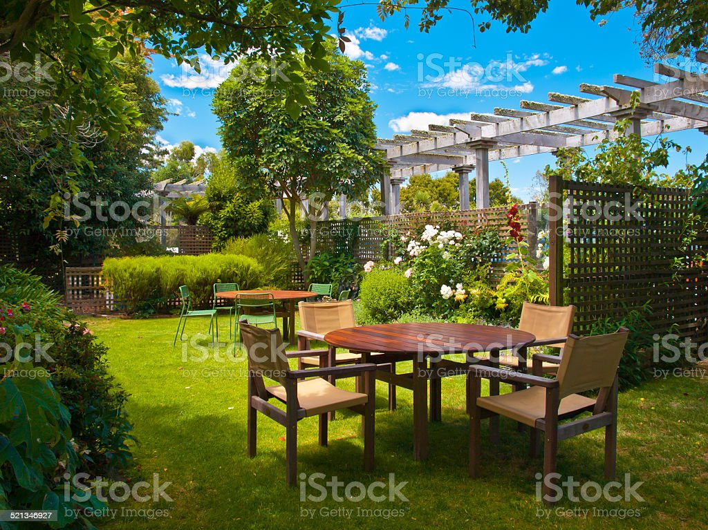 dining table set in lush garden stock photo