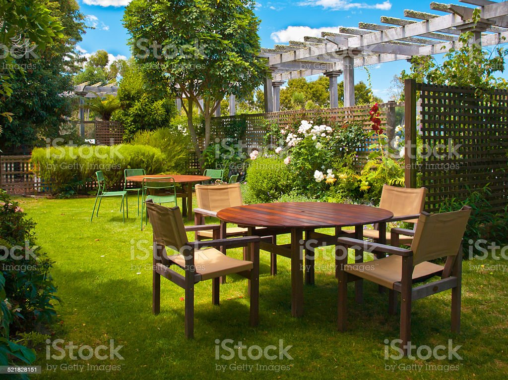dining table set in lush garden stock photo