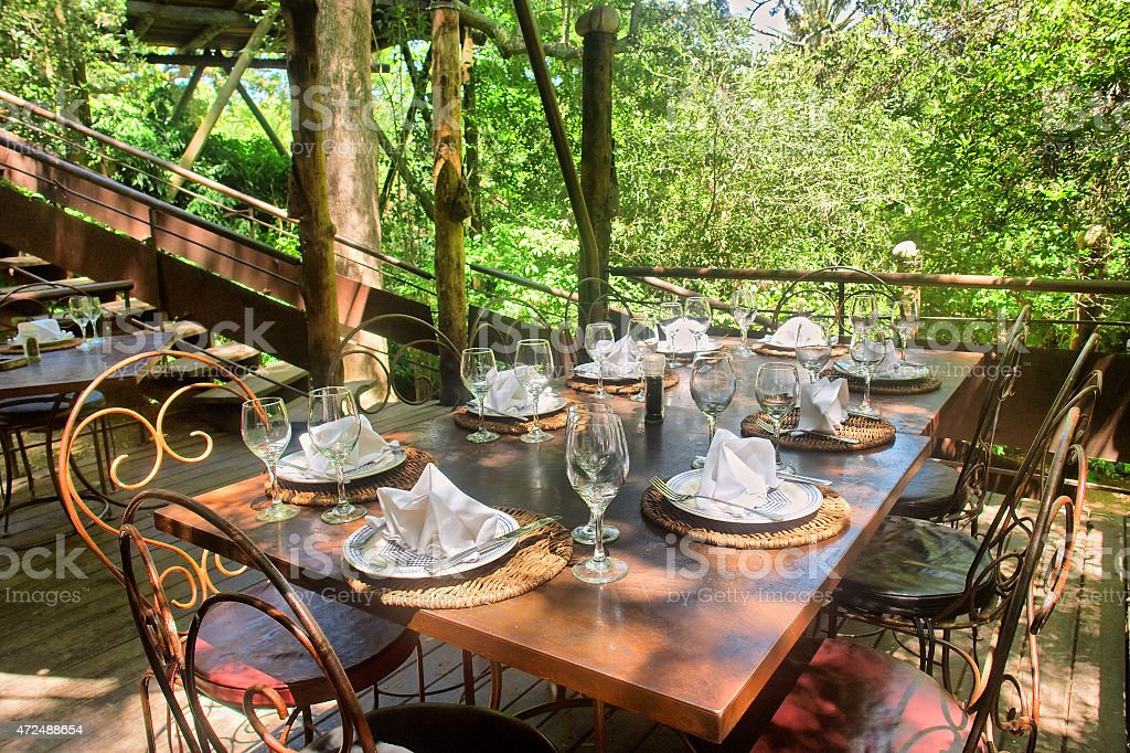Dining table under trees stock photo