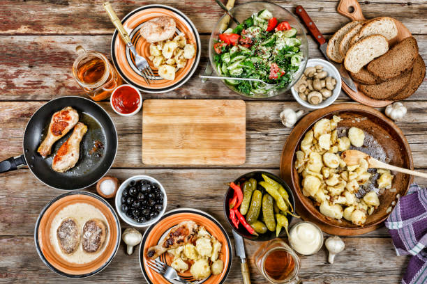 Dining table with a variety of dishes, grilled chicken legs, fried potatoes with vegetables in a frying pan, salad and snacks on a wooden table, top view - foto stock