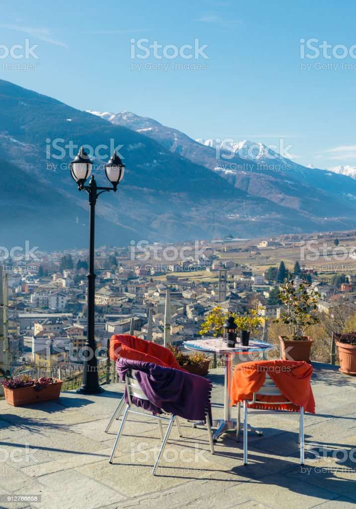 Dining table with a view overlooking Sondrio, an Italian town and comune located in the heart of the wine-producing Valtellina region stock photo