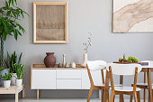 Dining table with fresh fruits and white wooden chairs in real photo of light grey room interior with two posters, green plants and small cupboard with decor