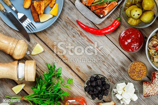 685404620 istock photo Dining table with grilled meat, rustic potatoes and pickled cucumbers. Concept of eating outdoors. 904049070