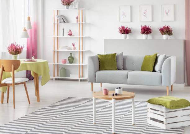 esstisch mit olivgrünen tischdecke in hellen skandinavischen wohnzimmer mit weißen und hölzerne möbel, grau sofa und gestreiften teppich, echtes foto - oliven wohnzimmer stock-fotos und bilder