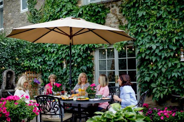 unter dem sonnenschirm garten mit freunden essen - sonnenschirm terrasse stock-fotos und bilder
