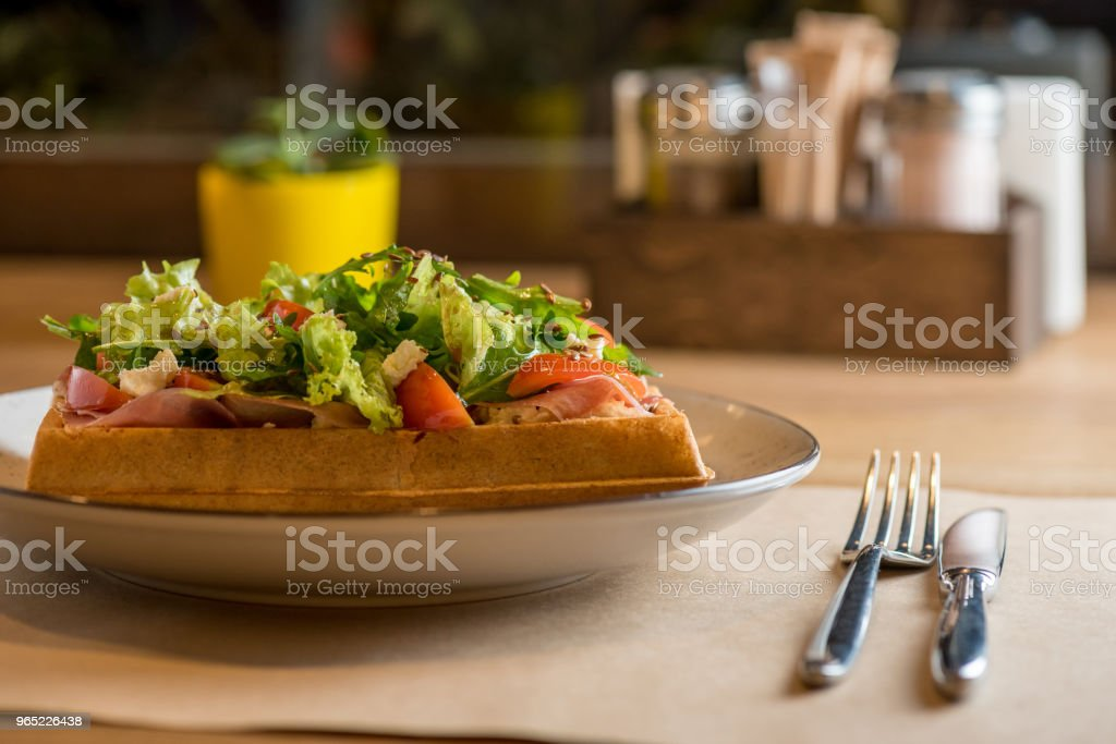 Dinner at cafe - Belgian Waffle with salad Iceberg, tomatoes and ham royalty-free stock photo