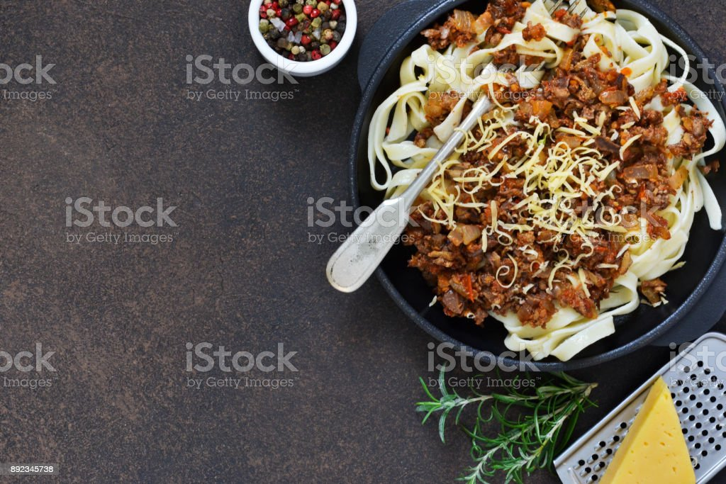 Dinner. Bolognese sauce with tagliatelle and parmesan cheese on a brown concrete background. stock photo