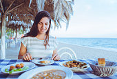 Woman eating in a seaside restaurant