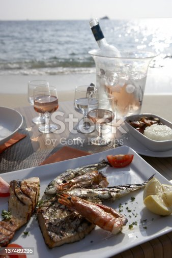 Lovely Seafood dinner set up on the beach in the early evening.Polarizer used to minimize sun glare
