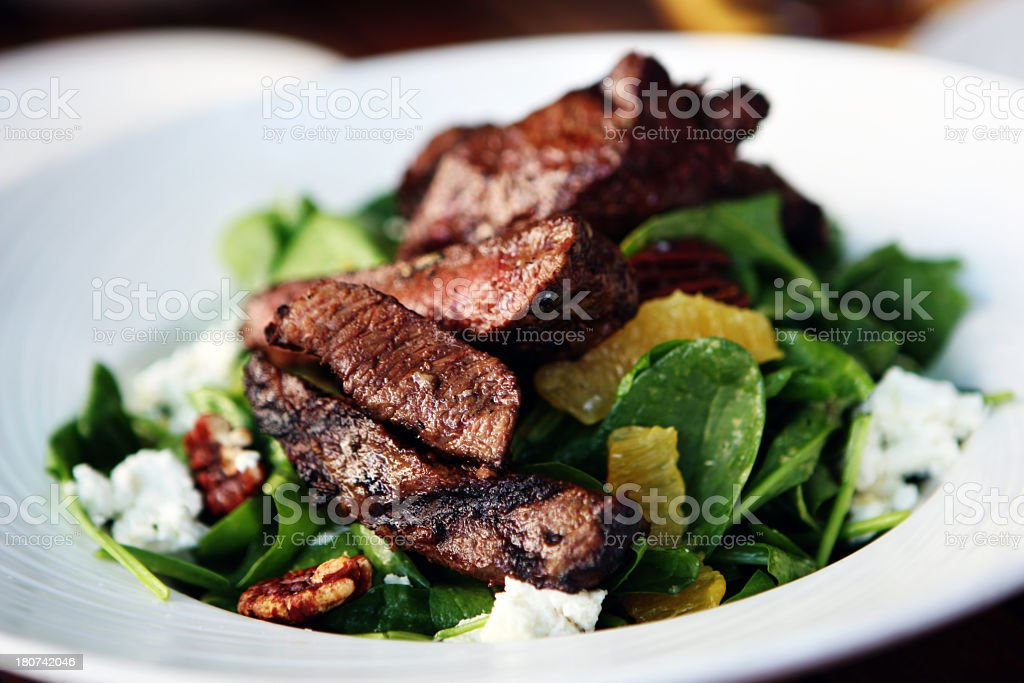 Dinner consisting of steak and a spinach salad stock photo