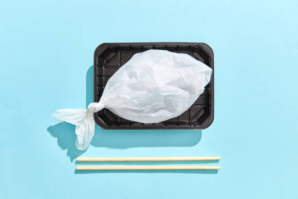Dinner container with fish from plastic bag served wooden chopsticks. stock photo