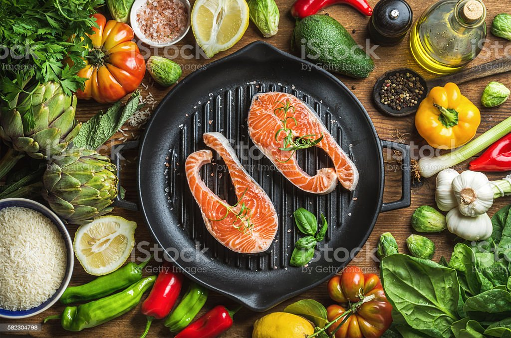 Dinner cooking ingredints. Raw uncooked salmon fish with vegetables, rice stock photo