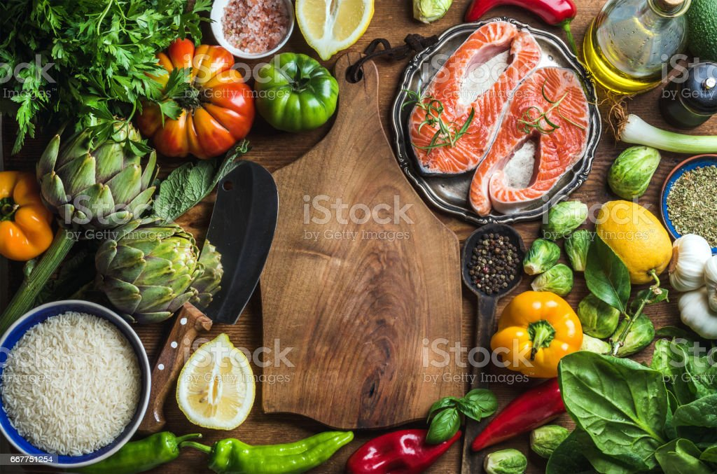 Dinner cooking ingredints. Raw uncooked salmon fish with vegetables, rice, herbs and spices over rustic wooden background stock photo