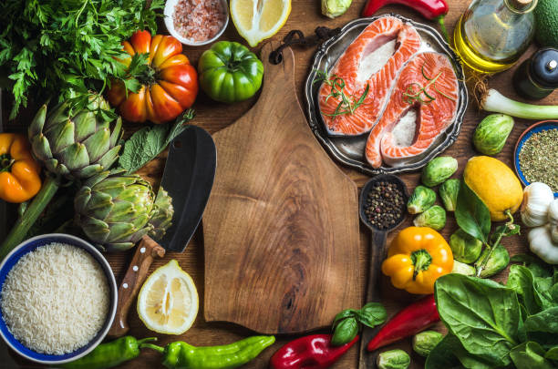 dinner cooking ingredints. raw uncooked salmon fish with vegetables, rice, herbs and spices over rustic wooden background - mediterranean food imagens e fotografias de stock