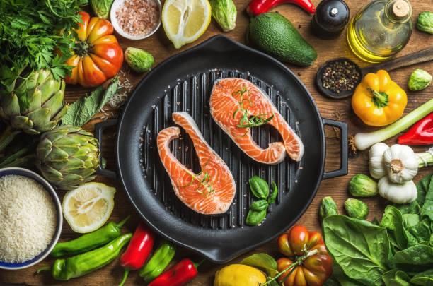 abendessen kochen ingredints. rohen ungekochten lachs fisch mit gemüse, reis, kräuter, gewürze und öl in grillen eisenpfanne über rustikale holz hintergrund - artischocken gesund stock-fotos und bilder