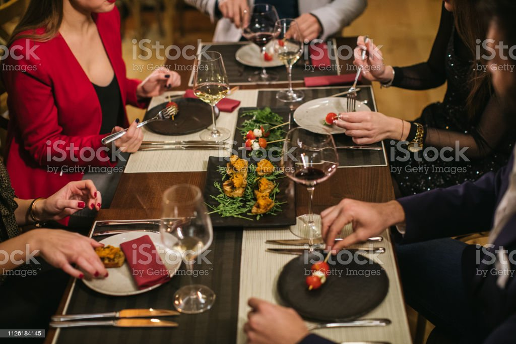 Unrecognizable people sitting at the table with food and wine in...