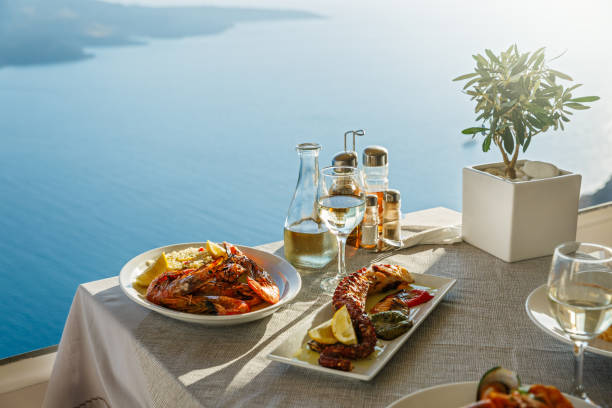 Dinner for two with fish dishes and white wine Dinner for two with fish dishes and white wine, a table on the background of the sea mediterranean sea stock pictures, royalty-free photos & images