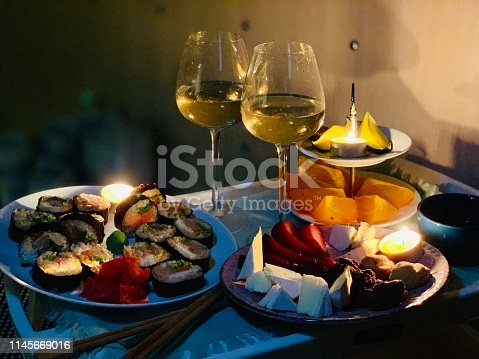 Dinner in bed on the food tray. Sushi, fruits, cheese and white wine.