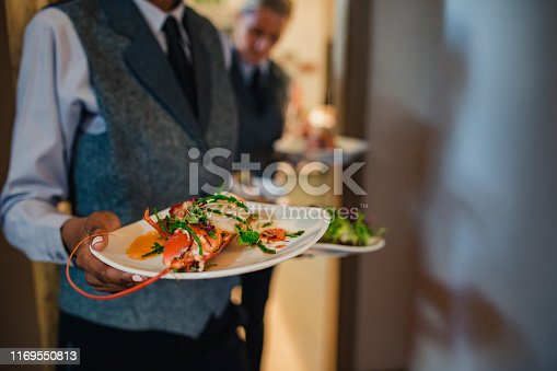 Two unrecognisable waiters are coming out of a hotel kitchen while holding two dishes each, ready to serve to guests.