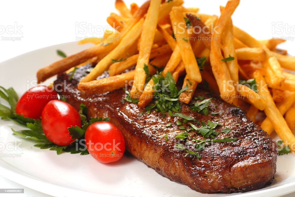 A dinner of steak and French fries stock photo