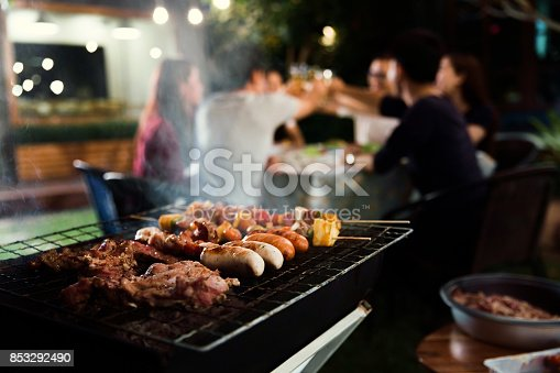 istock Dinner party, barbecue and roast pork at night 853292490