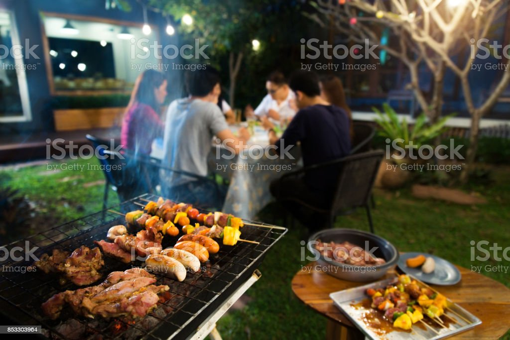Dinner party, barbecue and roast pork at night stock photo