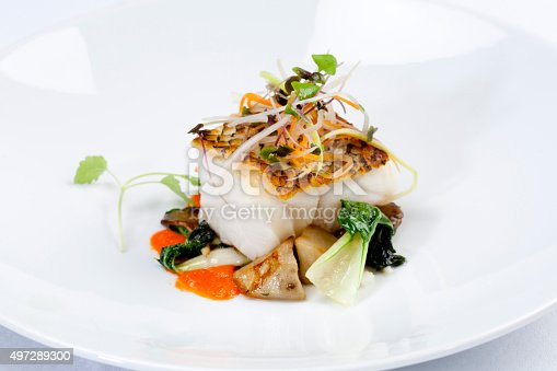 Grilled Sea Bass dinner, with vegetables on white plate.