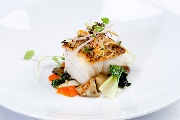Dinner Grilled Sea Bass dinner, with vegetables on white plate. fine dining stock pictures, royalty-free photos & images