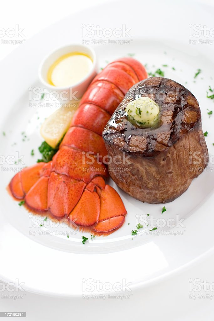Dinner plate with filet mignon and lobster tail with butter stock photo