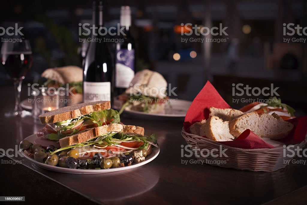 Dinner scene with wine, white bread & sandwiches stock photo