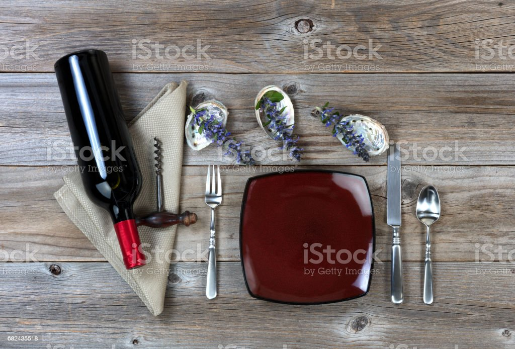Dinner setting along with red wine and nature decorations on rustic wood background royalty-free stock photo