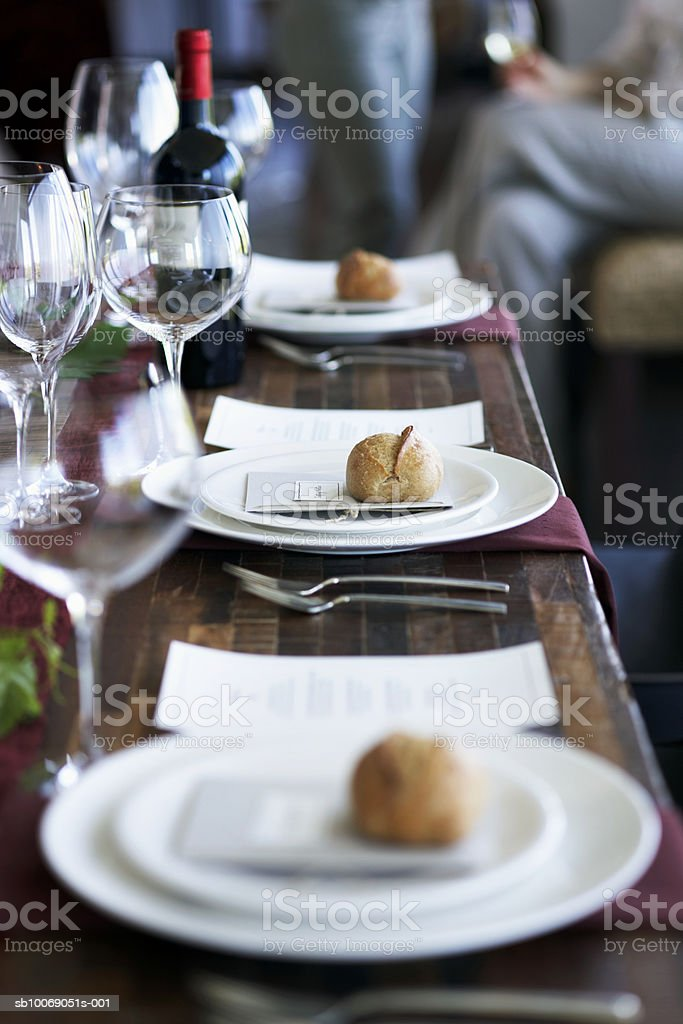 Dinner setting on table,  people in background 免版稅 stock photo