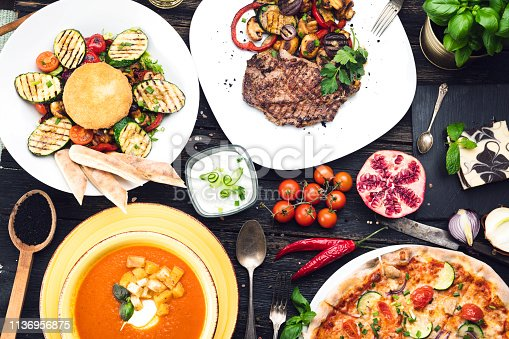 Grilled steak with grilled vegetables, salad, soup and pizza  on a dark wooden table, top view