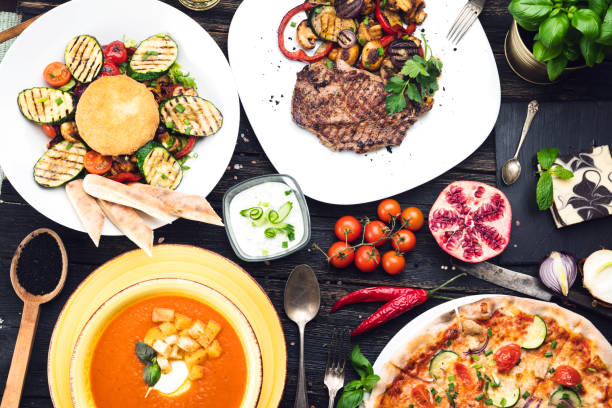 Dinner table full of food Grilled steak with grilled vegetables, salad, soup and pizza  on a dark wooden table, top view crockery stock pictures, royalty-free photos & images