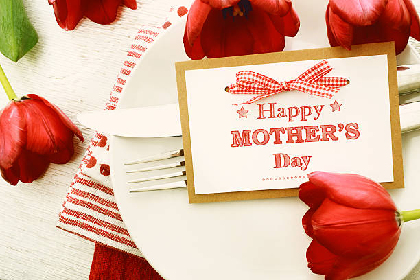 dinner table setting with mothers day message card and tulips - happy mothers day type stock photos and pictures
