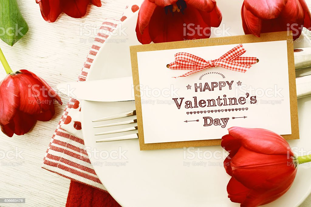 Dinner table setting with Valentines message and red tulips stock photo