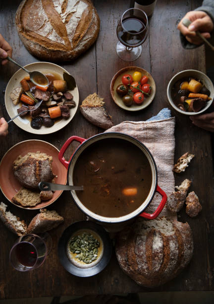 Dinner table with a meat stew food photography recipe idea Dinner table with a meat stew food photography recipe idea beef bourguignon stock pictures, royalty-free photos & images