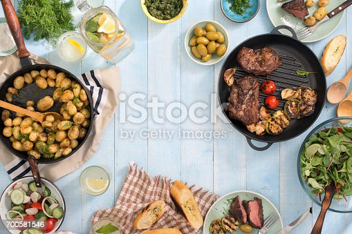 655793486istockphoto Dinner table with grilled meat, fried young potatoes, salad, snacks and homemade lemonade 700581546