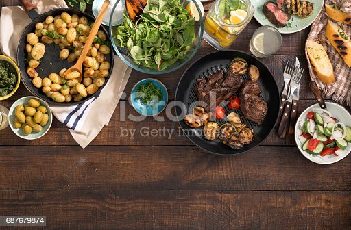 685404620istockphoto Dinner table with grilled steak, grilled vegetables, potatoes, salad, different snacks and homemade lemonade with border 687679874