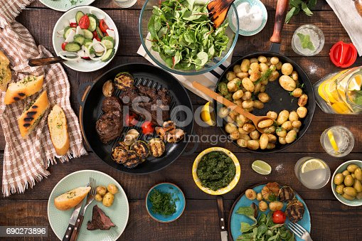 690274036 istock photo Dinner table with grilled steak, grilled vegetables, potatoes, salad, different snacks and homemade lemonade 690273896