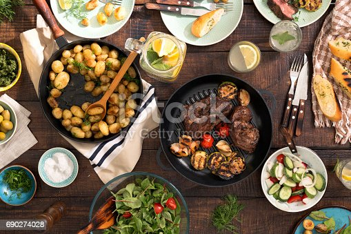 657146780 istock photo Dinner table with grilled steak, grilled vegetables, potatoes, salad, different snacks and homemade lemonade 690274028